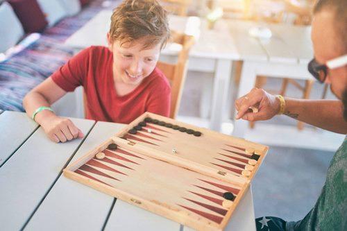 5f60b46f6ff278320d96c1cf boy and dad playing backgammon outside - شرایط تخته نرد انگلیسی که برای ماه مارس نیاز دارید